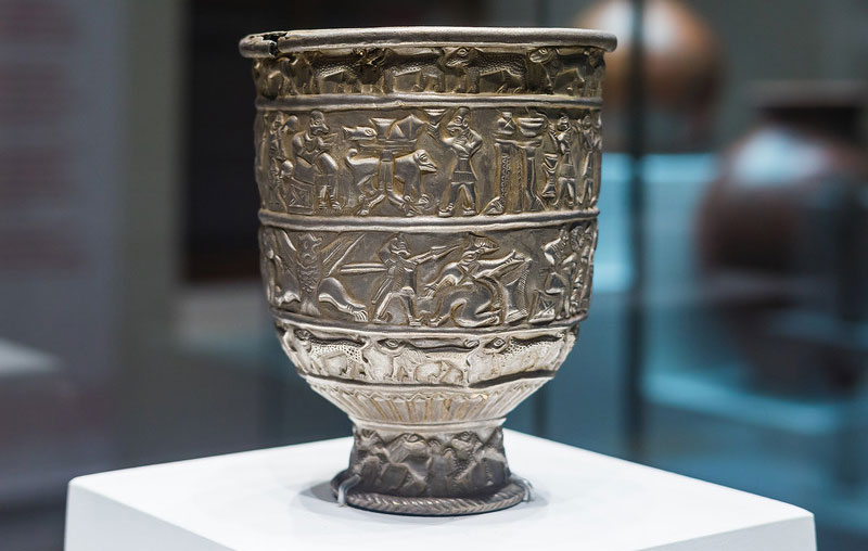 Silver goblet from Karashamb (Armenia), dating to the early second millennium BCE. In the main register, hunting and fighting are climaxed by a festive banquet, in which the ruler sits with cup in hand, attended by a cupbearer (in front of the table), servants with fly-whisks, and a harpist (behind him).